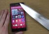 Il joue sur le smartphone Sony Xperia Z3 avec un couteau